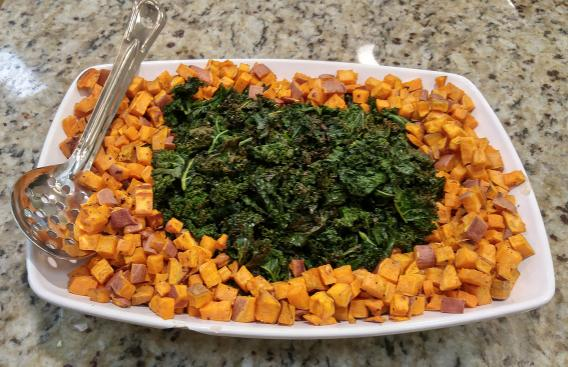 Roasted sweet potato and kale on a white plate.