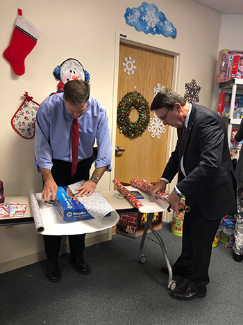 Governor Sununu and Demers wrapping gifts
