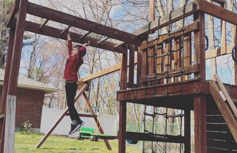Elliot Perry playing on a swingset