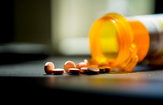 A bottle of pills that has fallen over and spilled pills.