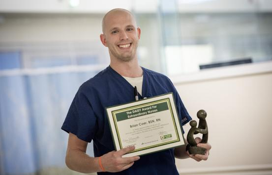 Brian Coer, BSN, RN, clinical nurse holding The Daisy Award certificate and statue.
