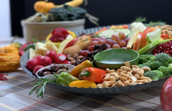Harvest Board arranged with fresh vegetables, nuts, fruit and dips.