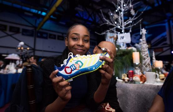 Aliyah holding a tennis shoe
