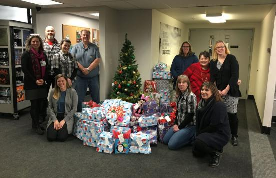 Staff from Moms in Recovery, Twin State Harley Davidson, and the Upper Valley Harley Owners Group with a pile of presents