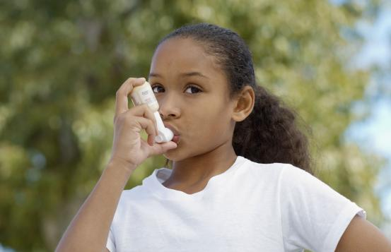 Young girl using an inhaler.