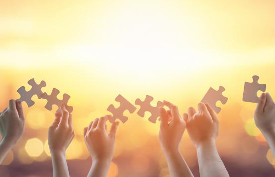 hands holding puzzle pieces against a yellow sky