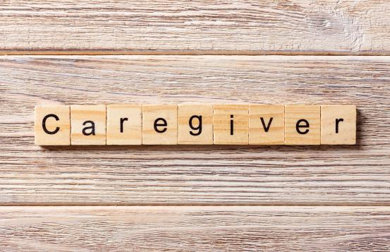 Word caregiver spelled out on Scrabble tiles