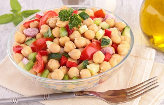 Clear bowl with chickpea, tomatoe, celery and cucumbers