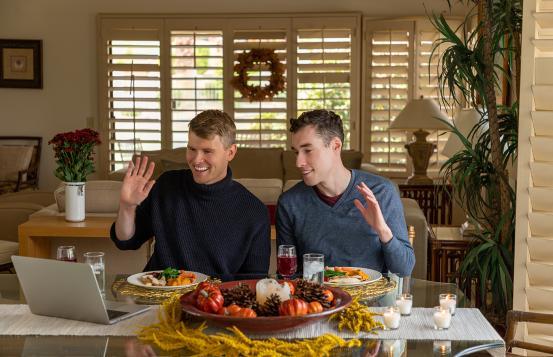 Two men eating dinner while having a virtual visit