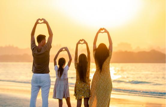 Family on beach making heart shapes with their hands.