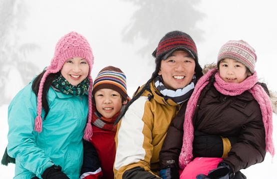 A smiling family in winter clothing