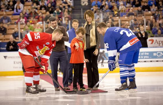 A child drops the puck to start a hockey game.