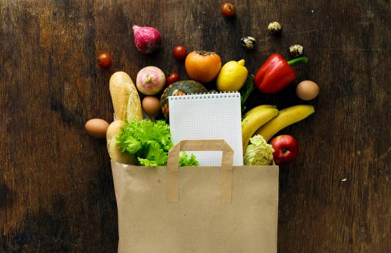 Healthy food spilling out of a paper grocery bag