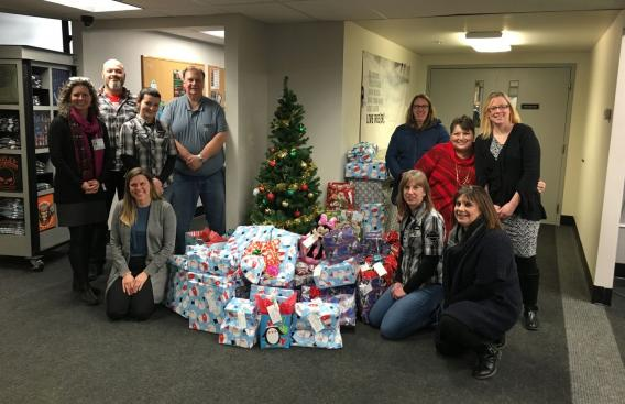 Staff from Moms in Recovery, Twin State Harley Davidson, and the Upper Valley Harley Owners Group with a pile of presents.