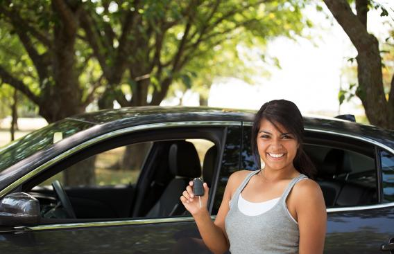 Female teen standing next to car with holding car keys.
