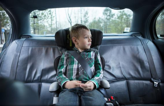 Young boy sitting in a booster seat
