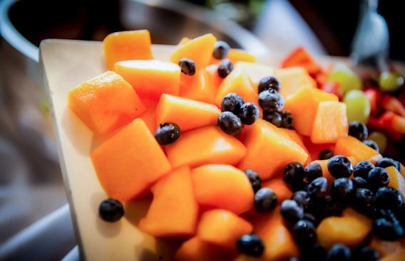 Cantaloupe cubes and blueberries on white platter.