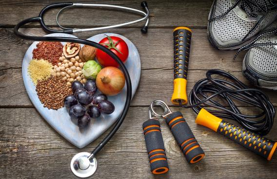 Healthy foods, exercise equipment, and a stethoscope