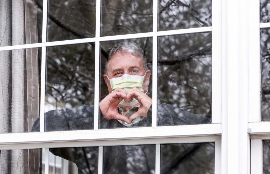 Senior behind window wearing mask.